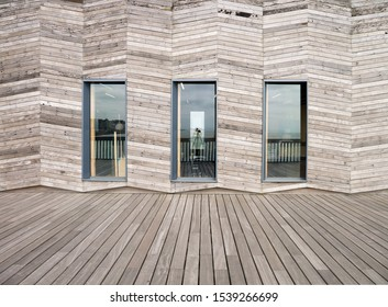 Colour image of three windows in a wood clad wall, with pier decking in front