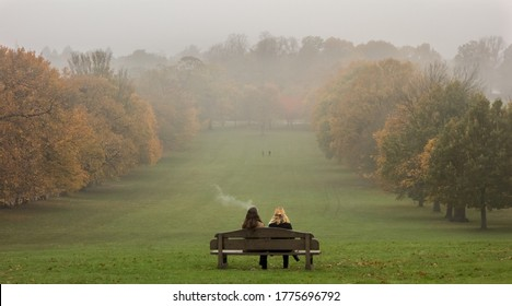 Colour image of two females sitting on a bench on the top of a hill. Taken in Wollaton Nottingham on 1st October 2019.