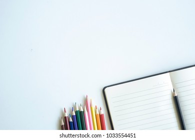 colour pencil with notebook paper and copy space on workspace.