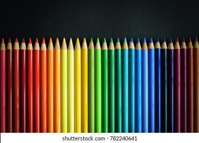 colour pencils  on a black textured background, lie horizontally in a row, view from above, copy space
