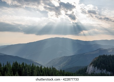 Colour picture of a beautiful scenery with the sun coming through the clouds over a mountain range