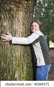 A colour portrait photo of a happy smiling forties man hugging a tree in the forest.