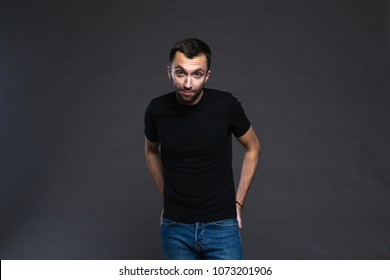 Colour portrait of a young handsome man in black t-shirt, hands on the waist, looking at the camera, against plain studio background.