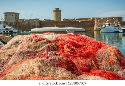 Coloured fishing net in the port of Livorno, Italy. In the background the famous old fortress of Livorno, Tuscany, Italy