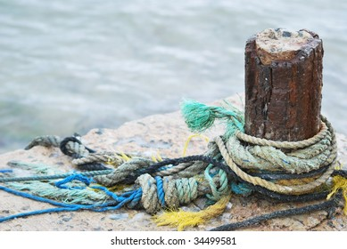 coloured fishing ropes on pier wooden pole
