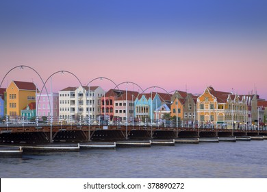 The coloured houses and the Queen Emma pontoon bridge of Willemstad, Curacao in the Netherlands Antilles at dusk.