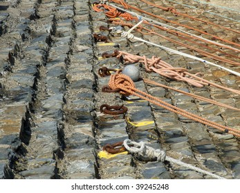 Coloured mooring ropes tied to rusty rings on harbour steps