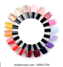 Coloured nail polish bottles stacked circle on a white background