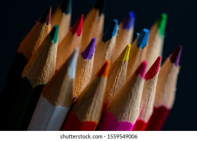 Coloured pencils isolated on black background close up. Top view. Macro Photoghraphy. Pencils Wallpaper. Bundle of rainbow colored pencils with selected focus on tips. Multicolored rainbow pencils.