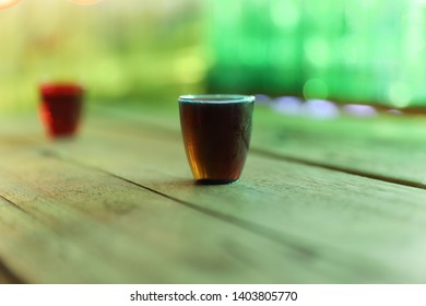 Coloured plastic tot glass with alcohol on a wooden table, selective focus