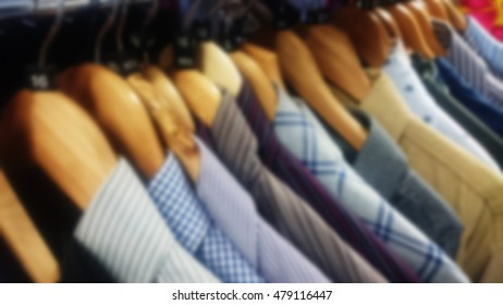Coloured shirts on wooden hangers. Out of focus.