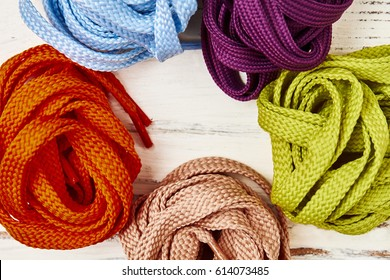Coloured shoelaces on wooden background. Ready to enjoy life.