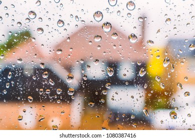 colourful abstact image of defocused houses through a window with raindrops. The reflection of the houses can be seen in the water drops