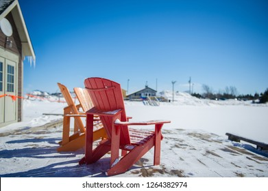 Colourful Adirondack chairs sitting on a patio covered with snow during a beautiful winter morning in Ontario, Canada. Buildings are visible in the background.