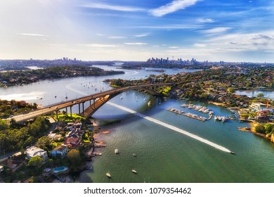 Colourful aerial view over Parramatta river and Gladesville bridge on Victoria road towards Sydney city CBD skyline. Speed boat beats the city traffic on open river water.