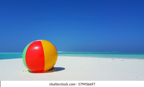 Colourful beach ball on the white sandy beach with blue sea and sky in summer