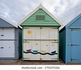 colourful beach hut painted with a sailing scene in pastel colours