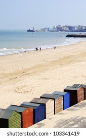 Colourful beach huts overlooking Margate Harbour