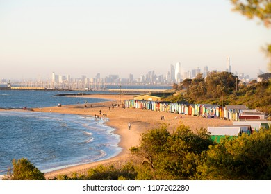 Colourful beach huts in a row with the Melbourne skyline as background.