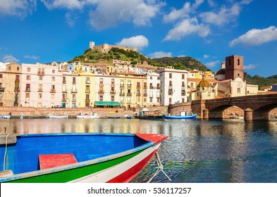 Colourful boat on the background of beautiful buildings of Bosa, Sardinia, Italy