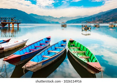 Colourful boats at shore of beautiful Phewa lake.  Pokhara, Nepal with Annapurna range in background. December 2017