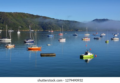 Colourful Boats in Waikawa Bay, New Zealand on a still summer morning with mist.