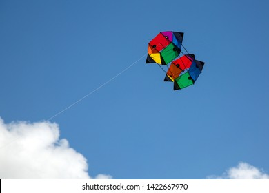Colourful box kite in primary colors flying high in the skay amongst the cloud