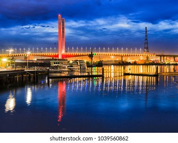 Colourful brightly illuminated Bolt Bridge in Melbourne Dockalns suburb over Yarra river at sunset reflecting in still waters against dark blue sky.