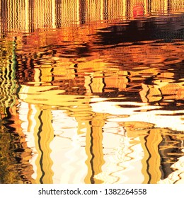 Colourful brown and green abstract design from reflections in water of the River Cam under the railway bridge in East Chesterton, Cambridge, UK.