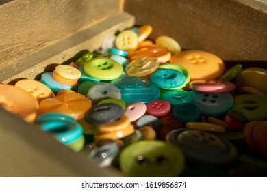 Colourful buttons in wooden box, selective focus, light and shadow
