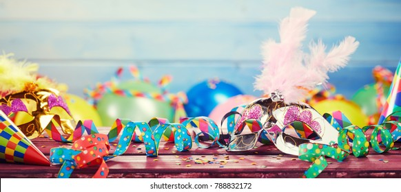 Colourful carnival panoramic banner with a jumble of party balloons, streamers, conical hats and confetti on a wooden table with copy space