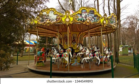Colourful carousel with white horses decorated  with ornaments. Merry-go-round on a gloomy day in winter in Krasnodar old park for children.