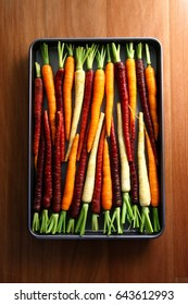 Colourful carrots in an oven tray on the wooden bench