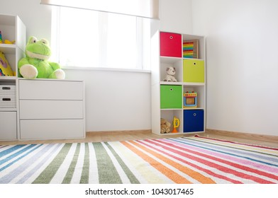 Colourful children rooom with white walls and furniture. Rainbow carpet at home interior with a window.