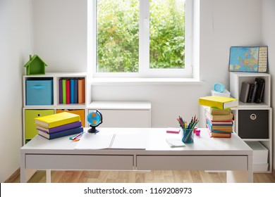 Colourful children rooom with white walls and furniture. Desk at home interior with a window