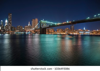 Colourful city lights at night from Brooklyn Bridge in New York City