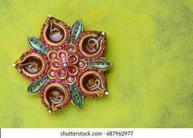 Colourful clay diya lamps lit on rangoli background on during Diwali celebration