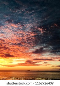 Colourful cloudy sunrise over ocean, and horizon with cargo ships on horizon, Eyre Peninsula, Spencer Gulf, South Australia
