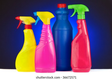 A colourful collection of bottles of janitorial supplies on a blue background