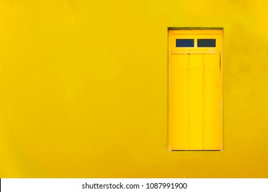 Colourful colonial Caribbean tropical style yellow facade closed window in a bright and intense yellow wall house background. Minimalist color toned concept image for tropical, summer, Caribbean.