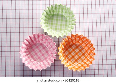 Colourful cupcake molds isolated on picnic cloth.
