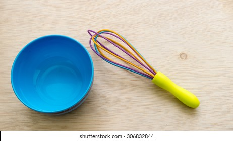 Colourful cute plastic whisk or egg beater and blue bowl on empty wooden surface. Concept of kitchen tool for kids or young chef. Slightly de-focused and close-up shot. Copy space.
