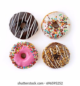 Colourful donuts with sprinkles on white background