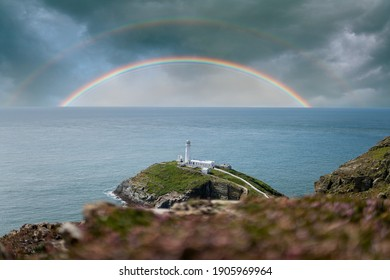 Colourful double rainbows in seascape over the ocean horizon with storm clouds dramatic sky and white lighthouse on top of island peninsular coastline in beautiful calm blue ocean sea south stack