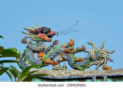 A colourful dragon made of tiles stands on top of a roof in Vietnam. Some green leaves of a tree are in the foreground. The background sky is blue.