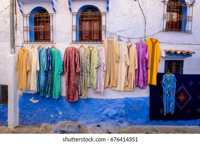 Colourful dresses for sale on an old wall in the Blue City Chefchaouen, Morocco