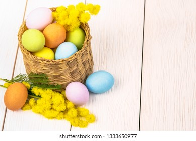Colourful Easter Eggs and Mimosa Flower in a Basket on a Wooden Table. Selective Focus.