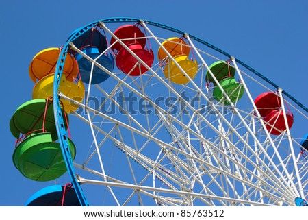 A colourful ferris wheel against a deep blue sky. Diagonal view