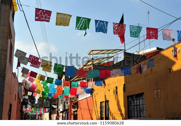 Colourful flages above a street with traditional Mexican houses in Mexico City, Mexico.