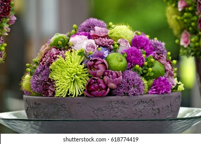 A colourful flower arrangement in a pottery dish